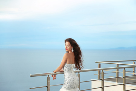 elegant girl: Brunette elegant woman in luxurious fashion white gown enjoying on balcony. Attractive girl with long blowing hair style. Stock Photo
