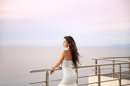Wedding portrait of Beautiful bride girl in beaded luxurious dress. Summer holiday fashion concept. Elegant woman enjoying on balcony looking sunset sky over sea.