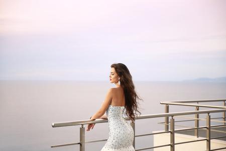 balcony: Wedding portrait of Beautiful bride girl in beaded luxurious dress. Summer holiday fashion concept. Elegant woman enjoying on balcony looking sunset sky over sea.