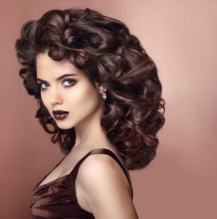 Bellezza ritratto di moda. Bella donna con labbra scure trucco e sano stile di capelli ricci. Acconciatura. Trucco per occhi. Modello di modo in costosi gioielli orecchino primo piano.