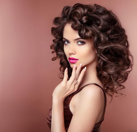 uñas largas: Maquillaje. Cabello. chica atractiva morena con el peinado rizado sano y labios de color rosa, las uñas cuidadas. Joyería de moda. Foto de archivo