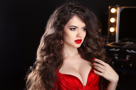 celebrities: Makeup. Hairstyle. Beautiful girl with long wavy hair. brunette model with red lips in sensual dress posing against of mirror with bulbs for make-up. Stock Photo