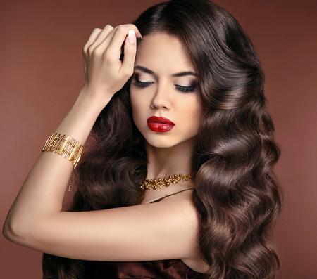 Healthy hair. Makeup. Beautiful brunette girl with long wavy hairstyle. Red lips. Elegant lady with jewelry.