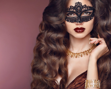 Healthy elegant hairstyle. Beautiful brunette girl model. Fashion golden jewelry. Beauty glamour woman wearing in venetian masquerade carnival mask. Standard-Bild