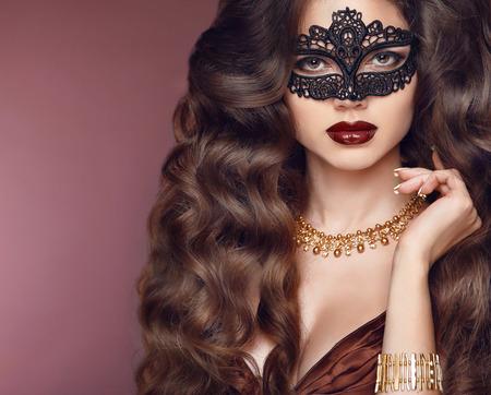 Gezonde elegante kapsel. Mooie brunette meisje model. Mode gouden juwelen. Schoonheid glamour vrouw, gekleed in Venetiaanse carnaval masker.