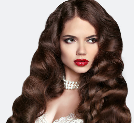 sexy bride: Bride Hairstyle. Healthy hair. Makeup. Beautiful brunette girl with long wavy hair style and Red lips. Elegant lady with jewelry. Wedding.