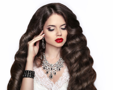 red lips: Cabello saludable. Maquillaje. Hermosa chica morena con el peinado ondulado largo. Labios rojos. Señora elegante con joyería. Mujer atractiva en caros colgante de primer plano Foto de archivo