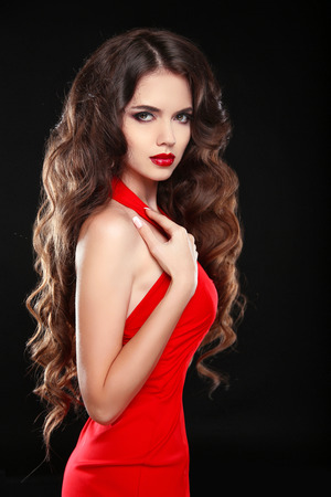 red dress: Beautiful girl with long wavy hair in red dress. Brunette with curly hairstyle posing isolaled on black background. Stock Photo
