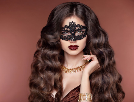 elegant hairstyle. Beautiful brunette girl model. Fashion golden jewelry. Beauty glamour woman wearing in venetian masquerade carnival mask. Stock Photo