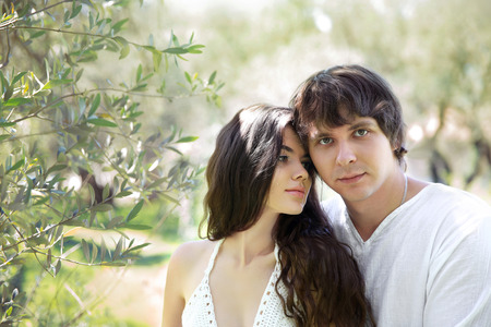 hansome: Romantic young couple outdoor portrait. Beautiful sensual brunette woman tempting hansome man in green park, springtime. Stock Photo