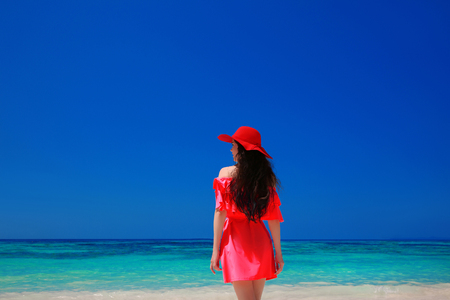 woman beach dress: Brunette Woman on azure sea,Tropical Beach. Attractive girl in red dress resting, outdoor portrait. Bliss freedom concept. Travel. Stock Photo