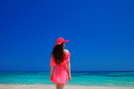 dress up: Brunette Woman enjoyng On Tropical Beach. Attractive girl in red hat and dress resting, outdoor portrait. Bliss freedom concept. Travel.