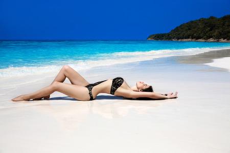sun tanning: Beautiful sexy bikini model woman lying on exotic tropical beach beside blue water by seashore. Summer vacation. Sun tanning girl on white sand.