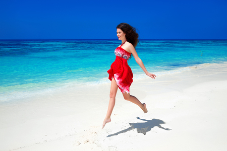 the good life: Beautiful free girl running on exotic beach with white sand and blue water. Happiness bliss freedom beach concept. Good life. Enjoyment. Summer Vacation. Nature background. Stock Photo