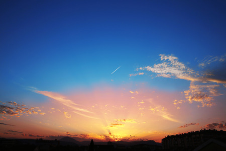 Sunset with clouds, light rays, blue sky, natural background. atmospheric effect