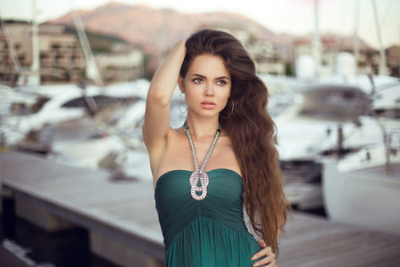Beautiful brunette girl model portrait with long hair posing by yachts marina at beach sunset. Summer holidays, vacation. Tivat, Porto Montenegro. Фото со стока