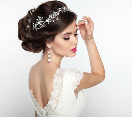 結婚式のヘアスタイル。美しいファッション花嫁少女モデルの肖像画。メイク。高級ジュエリー。茶色の毛のスタイリングと魅力的な若い女性