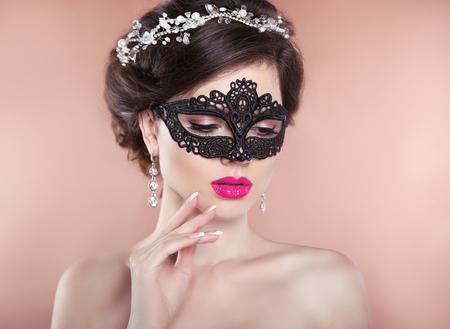 Bedenken. elegant kapsel. Mooie brunette meisje model. Gemanicuurde nagels. Fashion luxe sieraden. Schoonheid glamour vrouw, gekleed in Venetiaanse carnaval masker. Stockfoto