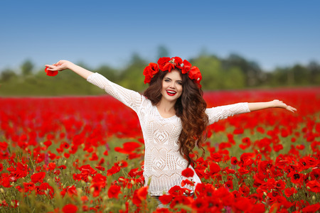 Beautiful happy smiling woman open arms in red poppy field nature background. Attractive brunette young girl model with curly hair and makeup laughing at camera Standard-Bild