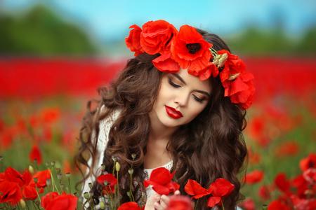 poppy: chica morena hermosa en flores de amapola fondo de la naturaleza campo rojo. Retrato de la belleza al aire libre. Mujer joven atractiva con los labios rojos y el estilo de pelo largo y rizado.