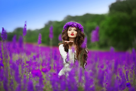 wild hair: Beautidul brunette teen girl sends an air kiss over wild flowers field nature background. Attractive young woman with wheat on head, long curly hair. Stock Photo