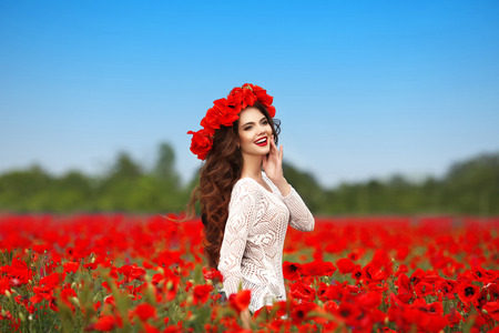 red poppies on green field: Beautiful happy smiling teen girl portrait with red flowers on head enjoying in poppies field nature background.