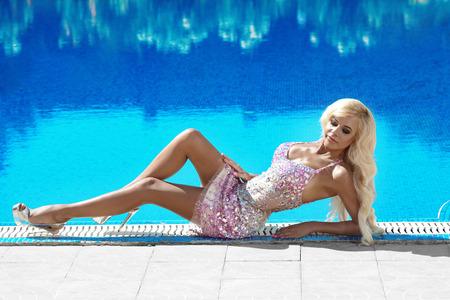 chica sexy: Recurso. Mujer hermosa modelo de glamour de la moda con el pelo ondulado largo en alineada de lujo con gemas de relax en la piscina Foto de archivo