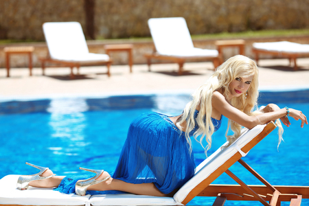 summer dress: Beauty fashion blond woman model posing in blue long dress on deck chair, near blue swimming pool, outdoor portrait.