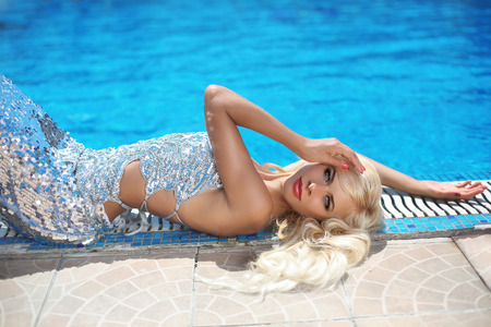 brilliant: fashion outdoor portrait of beautiful sensual woman with long blond hair in elegant dress relaxing beside swimming pool