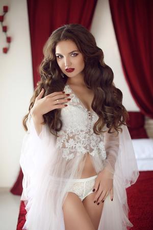 Belle mariage Bride femme portrait avec un style de cheveux bouclés, maquillage, porter en robe blanche sexy boudoir dressing posant sur le lit dans la chambre rouge et blanc. Banque d'images - 60887607