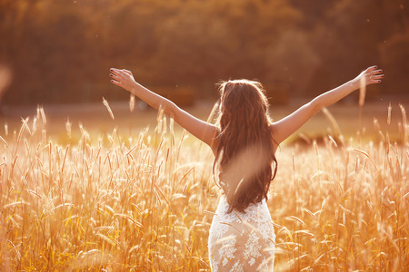 open hands: Enjoyment. Free woman arms outstretched. Happy bride with long wavy hair  wearing a white dress enjoying in wheat field at sunset.