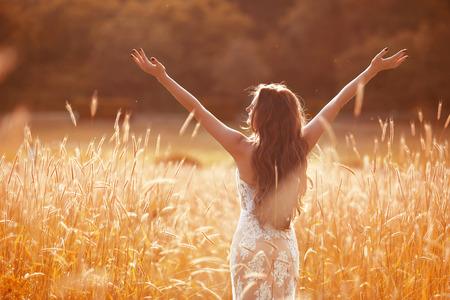 Genot. Vrije vrouw uitgestrekte armen. Gelukkige bruid met lang golvend haar, gekleed in een witte jurk genieten in een tarweveld bij zonsondergang.