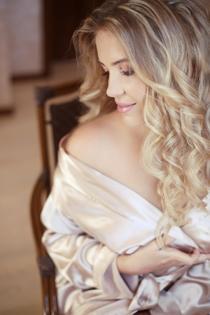Beautiful sexy bride woman. Wedding Makeup. Curly hairstyle. Attractive young girl model with long wavy hair wearing in white boudoir dressing gown, beauty portrait.