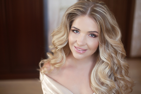 bridal salon: Long curly hair. Beautiful blond happy smiling bride girl looking at camera. Wedding makeup. Closeup portrait.