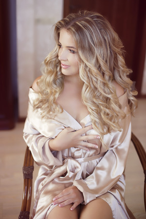 Long curly hair. Beautiful blond happy smiling bride girl looking at camera. Wedding makeup. Closeup portrait.