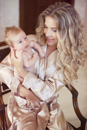 Beautiful mother with baby. Mom hugging her daughter child. Happy Family concept. Home indoor portrait. Stock Photo