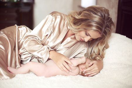 Beautiful mother calm baby lying on bed. Mom hugging her daughter child. Happy Family concept. Home indoor portrait.