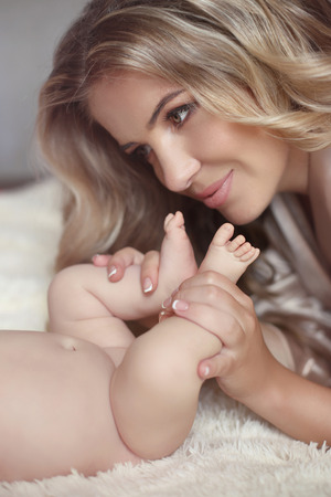 Close-up of happy Mother hugging Babys feet her Newborn baby girl. Little baby in moms hands. Beautiful woman with new born baby daughter relax in a white bedroom. Happiness. Stock Photo