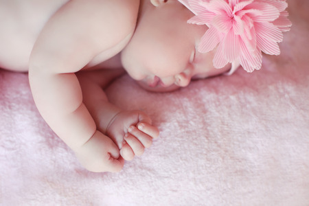 Close-up beautiful sleeping baby girl. Newborn baby girl with flower on head, asleep on fabric pink blanket. indoor portrait Stock Photo