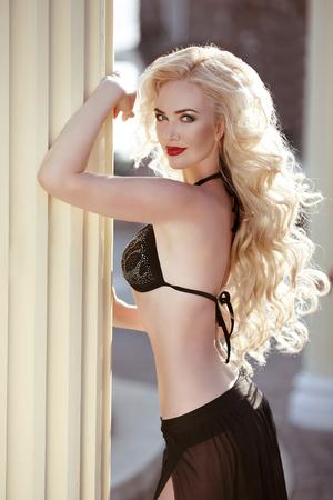 beautiful black woman: Long wavy hair. Beautiful sexy woman model in black bikini posing by column, summer vacation. Red lips makeup. Healthy body care.