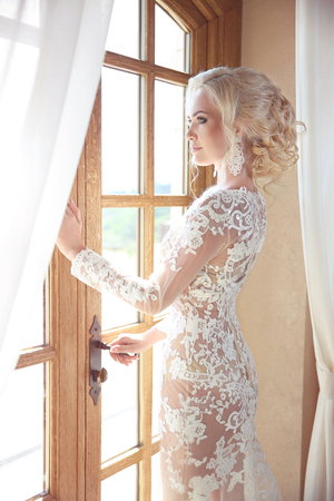 Beauty Portrait of elegant bride in wedding dress looking at window, indoors. Blonde young woman with makeup and blond hairstyle.