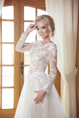 Portrait of beautiful bride in wedding dress against a window, indoors. Blonde young woman with makeup and hairstyle.