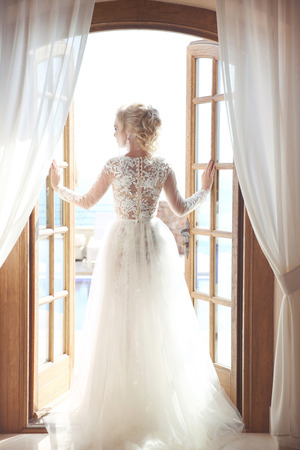 Young bride in gorgeous wedding dress with voluminous skirt looking at window, indoors. Blonde young woman. Stock Photo