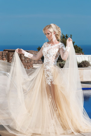 Happy blond bride in fashion wedding dress with blowing beige skirt, outdoor summer portrait. Slim young woman in luxury gown. Stock Photo