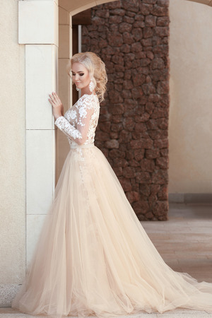 Elegant bride in fashion wedding dress posing by the wall. Attractive young blond woman in long gown. outdoor photo.