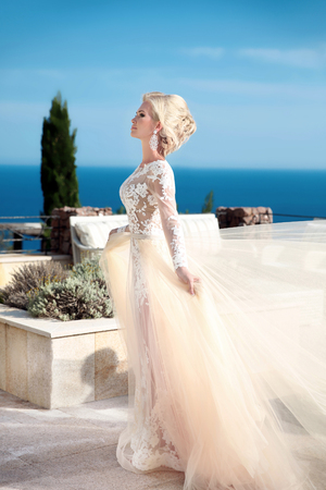 Beauty wedding Portrait of gorgeous bride in wedding dress with blowing skirt walking near swimming pool over blue sky, outdoor summer photo. Stock Photo