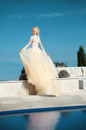 Beautiful bride in gorgeous  wedding dress with blowing skirt walking by water over blue sky, outdoor summer photo.
