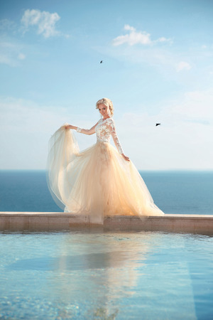 Beauty Portrait of gorgeous bride in wedding dress with blowing skirt walking on infinity swimming pool over blue sky, outdoor summer photo. Stock Photo