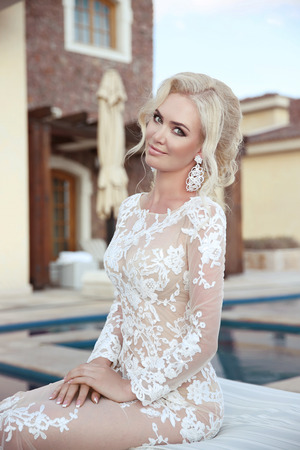 Wedding portrait of  blond bride woman with makeup, bridal jewelry and hairstyle. Beautiful model wearing in white fashion dress. outdoor photo.