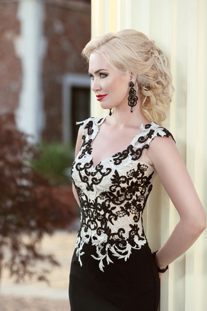 fashion girl: Beautiful blond lady in elegant dress. Hairstyle. Red lips makeup. Attractive fashion girl model in black evening gown. outdoor photo Stock Photo